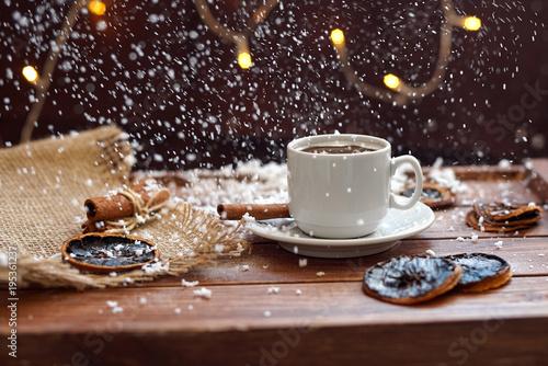 Fototapeta Чашка кофе с салфеткой из мешковины, сушеными дольками лимона и палочками корицы на деревянном коричневом фоне с огнями гирлянды под падающим снегом obraz