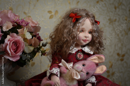 Photo Doll with blond curly hair in a red dress and a pink hare.