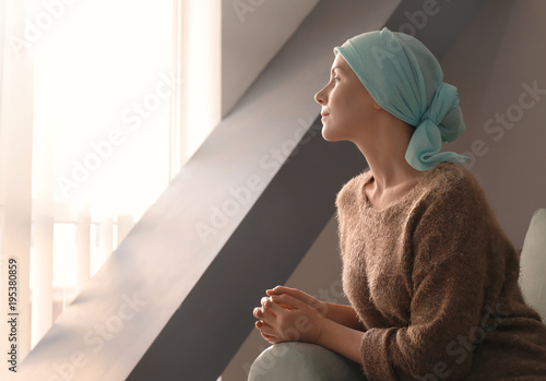 Fotografia  Young woman with cancer in headscarf indoors
