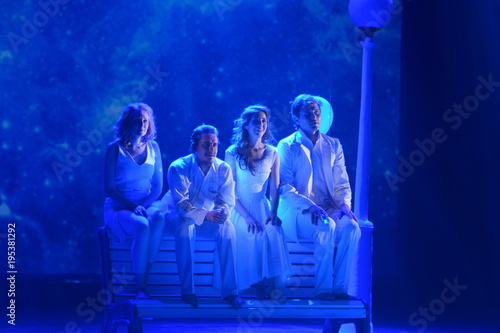 Photo  Young actors and Actresses sit on a bench on the stage of the theater