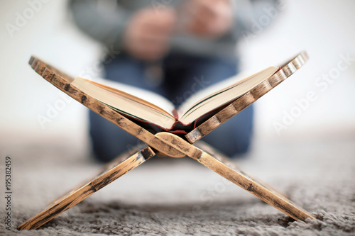 Open holy book of Muslims and blurred man on background
