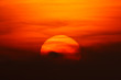 Leinwandbild Motiv red big sun obscured by clouds near the horizon at sunset or sunrise. The sun is partially seen through the clouds