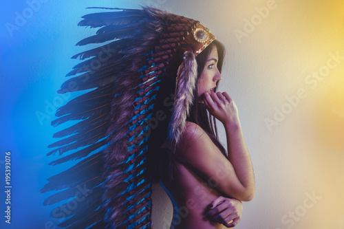 Beautiful young brunette with big American Indian plume of brown feathers Wallpaper Mural