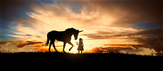 a sweet little girl offers fresh grass the Unicorn in a meadow at sunset