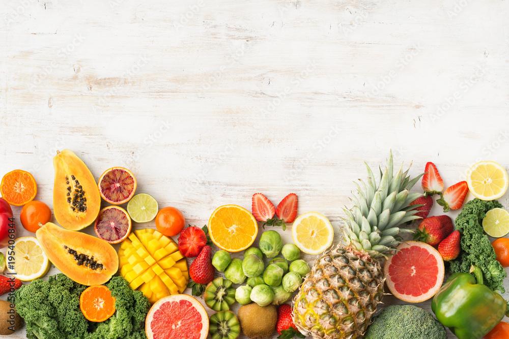 Fototapeta Fruits and vegetables rich in vitamin C, oranges mango grapefruit kiwi kale pepper pineapple lemon sprouts papaya broccoli, on wooden white table, top view, copy space, selective focus