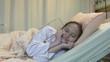 Happy Asian American tween girl in hospital bed