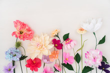 Crepe Paper Flowers On White Wooden Background