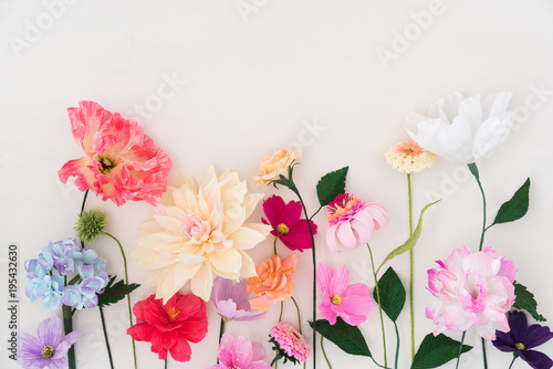 Foto Crepe paper flowers on white wooden background