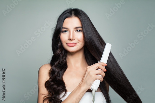 Cuadros en Lienzo Attractive Woman with Curly Hair and Long Straight Hair Using Hair Straightener
