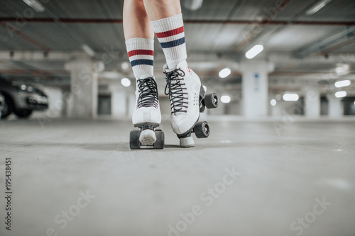 Stampa su Tela young sexy woman rollerskating in an urban looking garage and posing in a hipste
