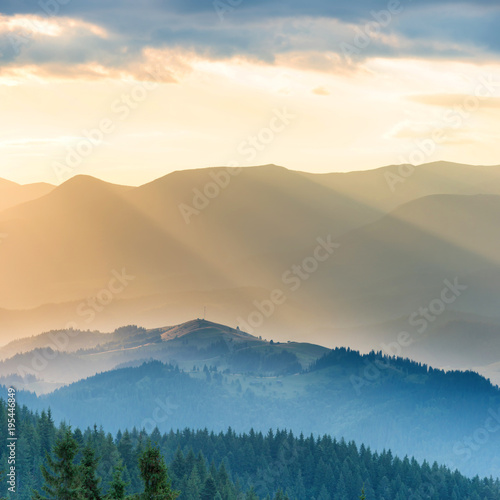 Beautiful sunset in the mountains. Landscape with sun shining through orange clouds
