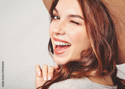 Fotomural  Portrait of young stylish laughing girl model in gray casual summer clothes in brown hat with natural makeup isolated on gray background