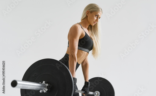 a63bbce3a947 Confident healthy young woman with barbell working out Female athlete  exercising with heavy weights at gym Bodybuilder performing deadlift  exercise with ...