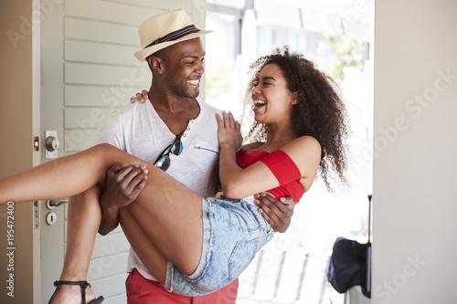 Fotografia  Man Carries Woman Over Threshold Of Honeymoon Rental