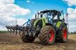 canvas print picture - Ackerbau - Traktor mit vorgebauter Egge beim Maislegen