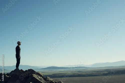 Photo Retrato de hombre a contraluz en la cima de una montaña rocosa