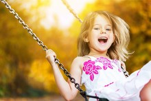 Little Child Riding On A Swing