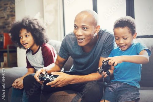 Fotografia African American family at home sitting in sofa couch and playing console video games together