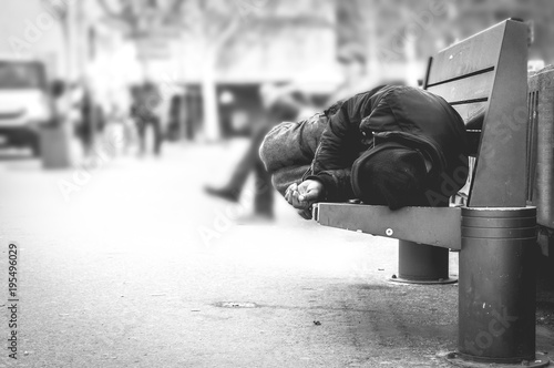 Poor homeless man or refugee sleeping on the wooden bench on the urban street in Fototapeta