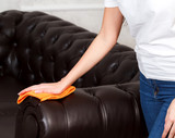 shot of female hand wiping brown leather chester couch or sofa