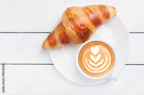 Leinwand Poster coffee croissant view from above wooden background white