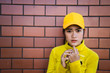 Portrait asian hipster girl on brick wall background,she wear yellow tone full body,Lifestyle of thailand people