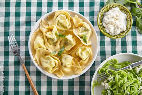 Plakat Napowietrznych obraz tradycyjnych włoskich ravioli z serem ricotta i tagliatelle szpinaku na stole pokryte zielonym obrus w kratkę