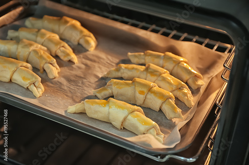 Raw croissants on baking sheet in oven Canvas-taulu