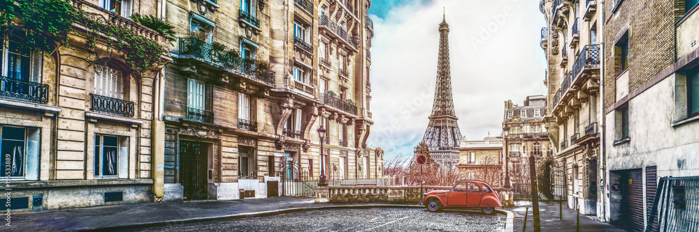 Fototapeta The eiffel tower in Paris from a tiny street with vintage red 2cv car