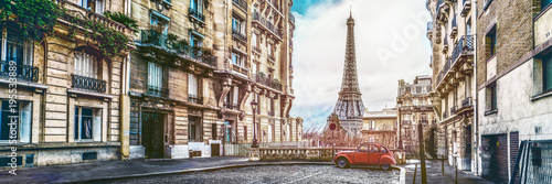 The eiffel tower in Paris from a tiny street with vintage red 2cv car