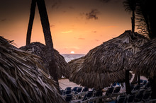 Sunrise And A Thatched Palm Frond Palapa On A Beautiful Caribbean Beach At Dawn.