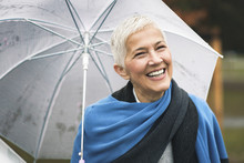 Happy Senior Woman Enjoying Rainy Weather Outdoors In A Park, Holding An Umbrella