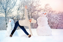 Young Woman  Practicing Triangle Yoga Pose Between Two Snowmen