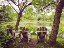 Wooden Chairs Near A Pond In T...