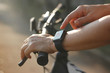 Female cyclist hands with heart rate icon on smart watch, bicycle in summer trail. All on screen are designed up.