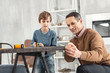 Happy family. Nice content little fair-haired boy holding a measuring tape and measuring the table and his daddy helping help