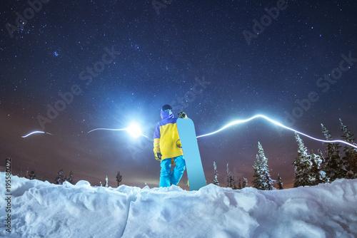 Fotografía  Lady snowboarder night photo against night mountains