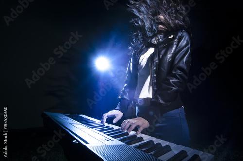 Fototapeta Girl playing keyboard on stage