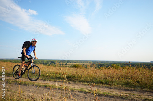 Spoed Foto op Canvas Noordzee Male cyclist with backpack driving by rural dirt road outdoors