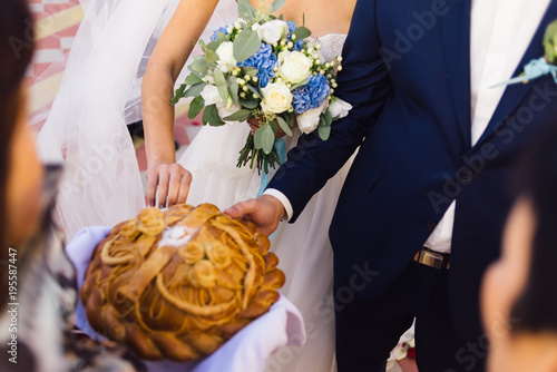 The bride and groom break a piece of wedding bread Canvas Print