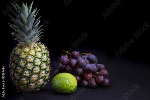 dark food chiaroscuro lighting on pineapple grapes and lime with