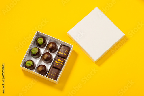 Assortment of luxury bonbons in box on bright yellow background