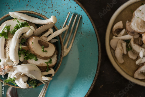 Blue Plate full of various types of edible mushrooms with parsley and garlic.