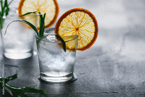 Valokuvatapetti Two shots of cocktails with ice, dried orange slice and fresh tarragon on a grey table