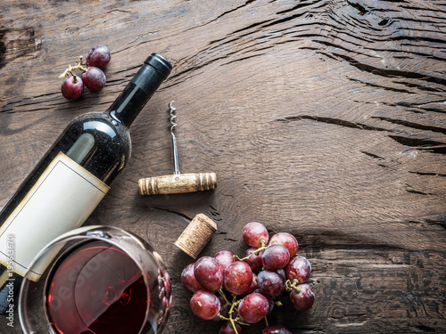 Fotomural  Wine glass, wine bottle and grapes on wooden background
