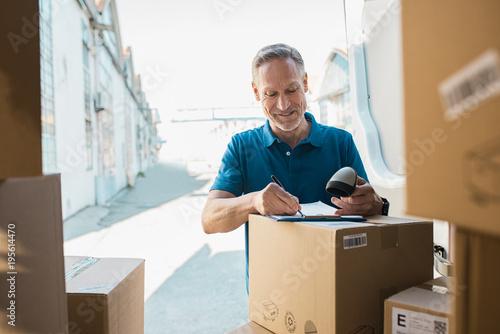 Fotografie, Obraz  Delivery man updating checklist