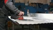 Manual sander sanding a metal detail at the factory