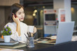 Young Asian female entrepreneur talking on the phone while working at home office.