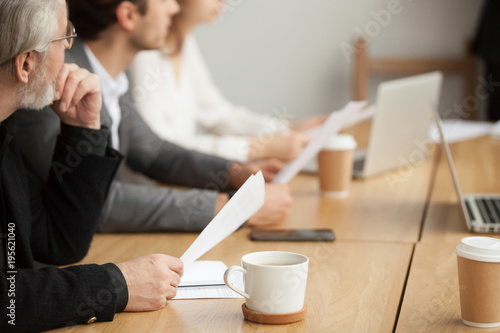 Fotografía  Attentive senior businessman holding documents focused on listening at group mee