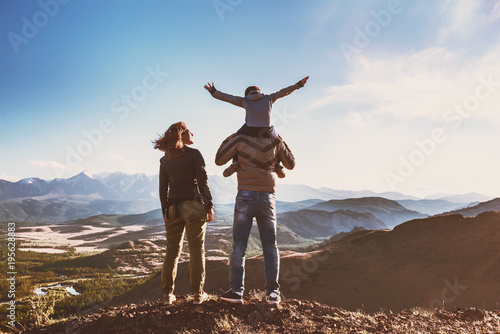 Happy idyllic family against mountains is having fun